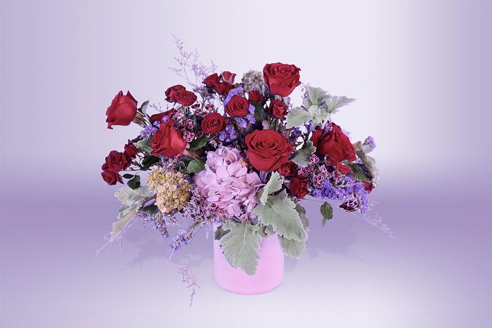 Arreglo floral natural con base rosa con hortensia follaje